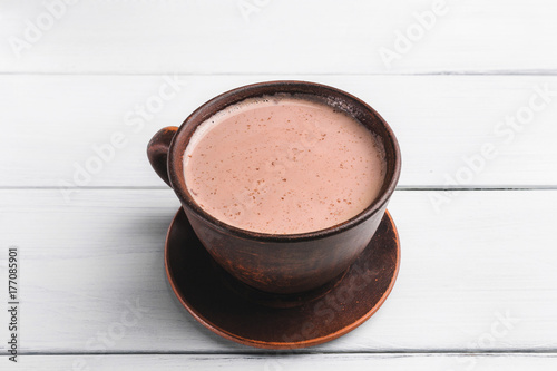 Foto op Canvas Chocolade Hot cocoa with milk in brown clay cup, on table of white wooden planks