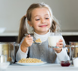 Cute little girl with milk and healthy oatmeal at  kitchen - 177086955