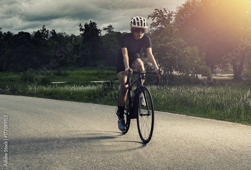 Asian healthy Cyclist girl wearing helmet Cycling and exercise on bicycle in track and open road and cross process and soft flare filter work out and sport concept