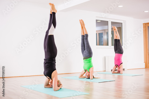 Fotobehang School de yoga Three girls practicing yoga, Sirsasana / Headstand pose