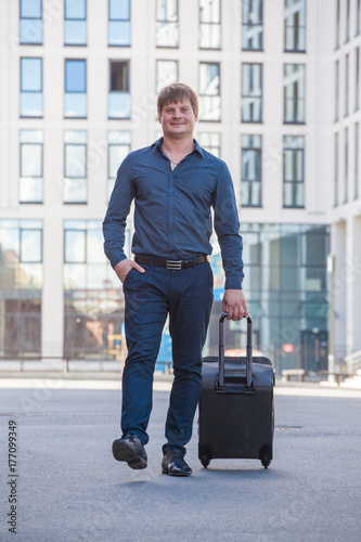 A man with a black suitcase in the background of a skyscraper. Moving to a new apartment. Departure on vacation. Stuart.