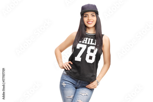 Young woman in a hip-hop outfit leaning against a wall Poster