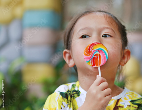 Adorable little laughing girl holding big colorful lollipop. Poster