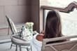 Woman relaxing at balcony enjoying breakfast.