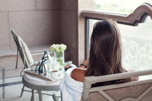 Woman relaxing at balcony enjoying breakfast. Poster