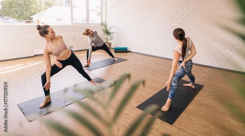 Plakat Three people practising yoga in class