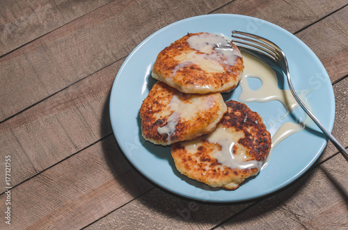 Appetizing sour cream with cream on a blue plate on a wooden dark background