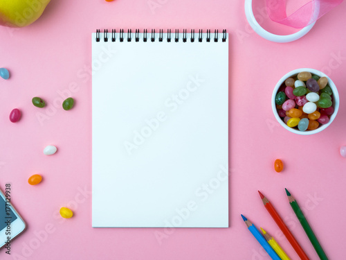 Open notebook with a clean white sheet, sweets, mobile phone, crayon, decorations on a pink bright table. Girl's workplace for creativity, plans and dreams