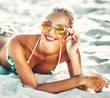 Beautiful girl on a summer beach in sunglasses - close up