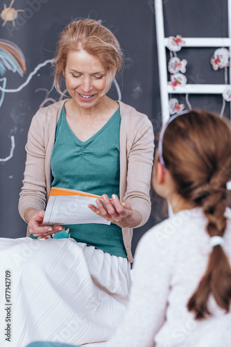 Teacher listening girl singing song