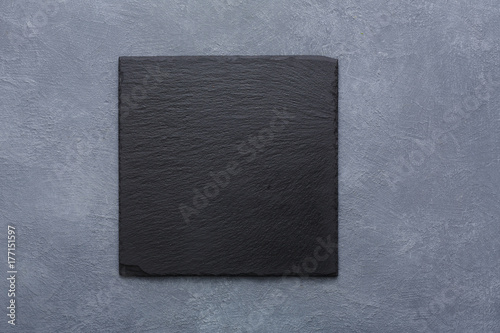 Empty square black slate plate on rustic grey backround copy space