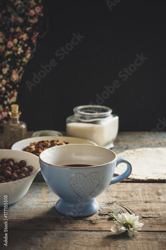 Wall mural on the table a cup with a hot drink and cornflakes