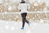 man running along snow covered winter bridge road - 177161709