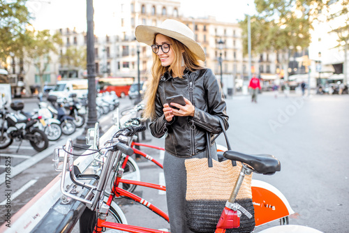 Poster Young woman tourist renting a city bicycle with smartphone in Barcelona