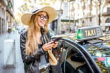 Young woman tourist using a smart phone standing near a taxi car on the street in Barcelona city - 177164100