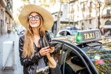 Young woman tourist using a smart phone standing near a taxi car on the street in Barcelona city - 177164124