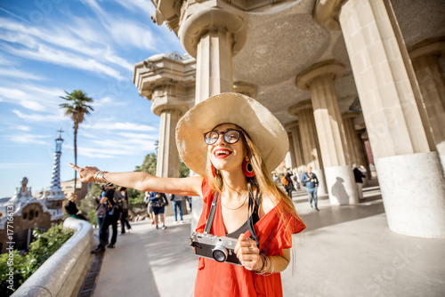 Happy woman tourist in red dress with hat standing near the columns visiting famous Guell park in Barcelona