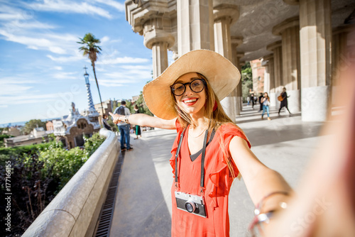 Papiers peints Barcelona Happy woman tourist in red dress with hat standing near the columns visiting famous Guell park in Barcelona