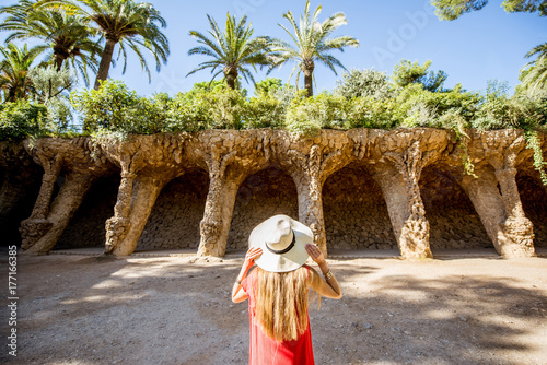 Young woman tourist in red dress enjoying beautiful columns of viaduct in Guell park in Barcelona