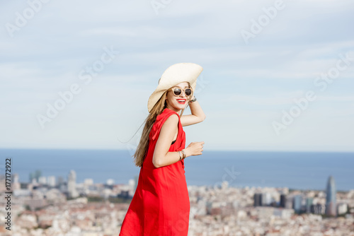 Young woman tourist in red dress with hat enjoying great cityscape view on Barcelona