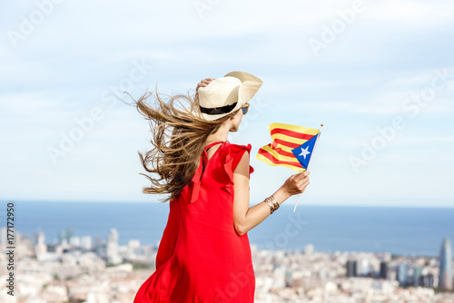 Young woman tourist in red dress with hat and catalan flag enjoying great cityscape view on Barcelona