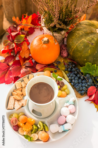 Wall mural Fondue with chocolate and marshmallows -  autumn composition with pumpkin in the background