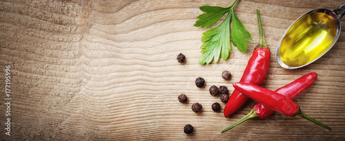 Red chili peppers, peppercorns, parsley and extra virgin olive oil on wooden background