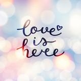 love is here lettering, vector handwritten text on blurred lights