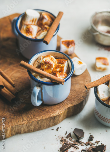 Papiers peints Chocolat Hot chocolate in enamel mugs with cinnamon and roasted marshmallows over grey marble background, selective focus
