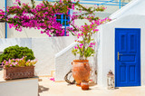 Traditional white-blue greek architecture and pink flowers. - 177229191