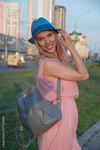 Beautiful blond girl in hat in pink dress with backpack on back in city park Poster