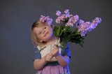 Little girl with a bouquet of lilac, mother's day