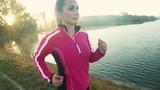 A young woman running  at lake at sunrise. .camera stabilizer shots. - 177245195