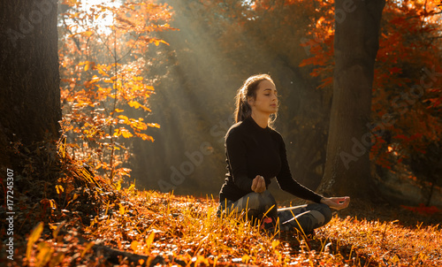 Wall mural A young woman make yoga position at sunrise. in the autumn forest.