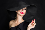 Elegant woman, femme fatale in black hat with cigarette in hand. On black background - 177248359