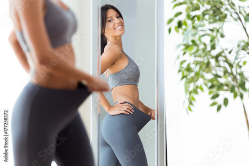 Beautiful young woman looking herself reflection in mirror at home.