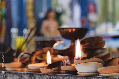 Burning old textured candles with defocussed background of the most popular Hindu shrines outside India - Batu Caves Poster