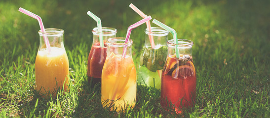 Healthy detox colourful drinks on green summer grass. Natural, fresh, organic juices and tea in bottles. Diet, well being and weight loss, superfoods, health, vegetarian food concept