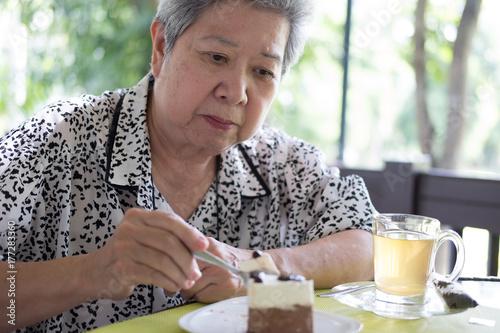 Poster elder senoir eating chocolate mousse cake at cafe