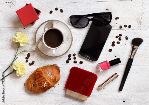 Coffee with croissant and make up tools