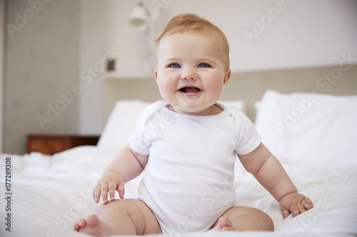 Happy Baby Boy Sitting On Parents Bed Poster