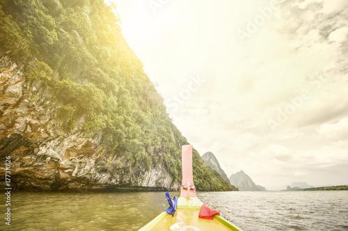 A long tail boat is sailing in the Ao Phang Nga (Phang Nga Bay) National Park at sunset Poster