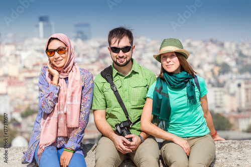 Group of multiracial happy Friends sitting near the mosque and enjoying view of Poster