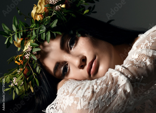 Plakát Beautiful portrait of young woman with wreath of flowers lying on a floor