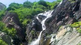 Slow motion shot of rocky waterfall, panning down from the top - 177354934