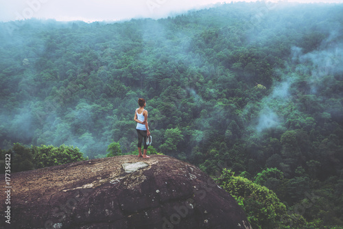 Asian women travel relax in the holiday. Standing hands on a rocky cliff. Wild nature wood on the mountain.