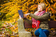 Woman relaxing sitting on bench in park using tablet