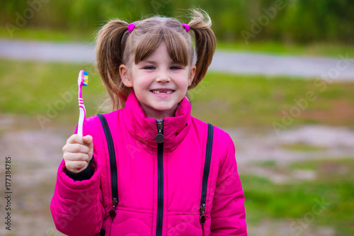 Cute little girl holding a toothbrush Poster