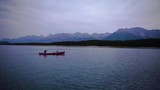 Wide shot of small family canoeing on beautiful day, colourful sky and mountains above - 177385560