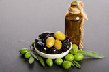 Black and green  olives  mixed in the  porcelain bowl and Virgin olive oil in a glass bottle on gray background - 177386198